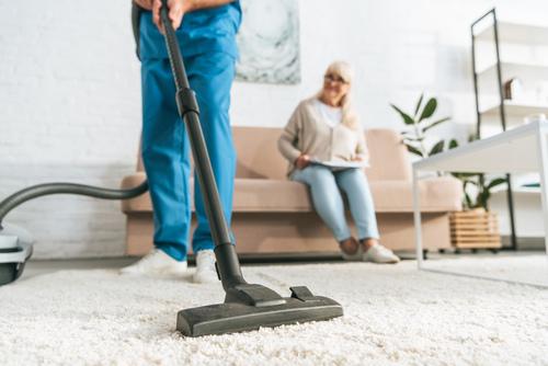 Limpiando alfrombra en casa de mujer
